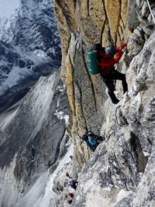 Climber descending below grey tower on Ama